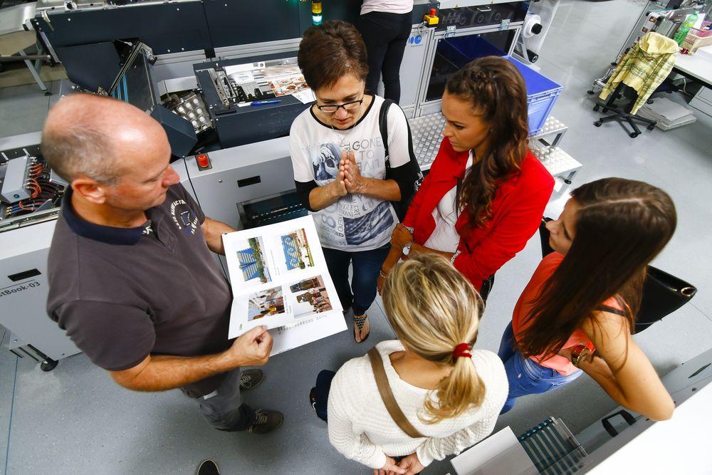 Jednatelka společnosti HappyFoto Michaela Bílá Čížková vysvětluje v rakouské laboratoři vítězkám, jak se vyrábí fotokniha.